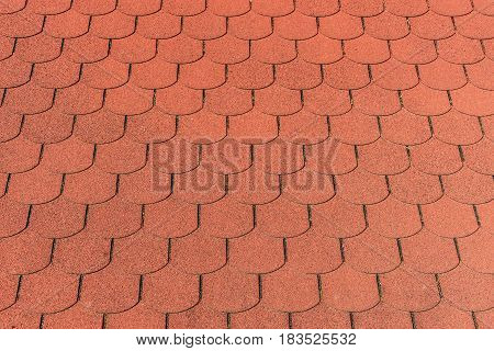 Closeup detail of red bitumen shingles on a roof