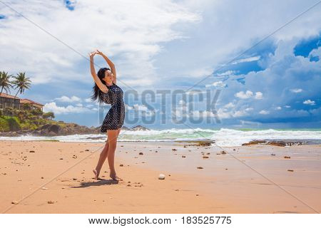Fashion woman walking on the beach. Happy lifestyle. Sand, blue cloudy sky and ocean waves. Vacation at Paradise. Ocean beach relax, travel