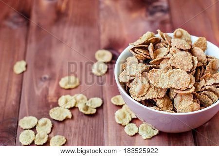 Flakes for breakfast in a deep plate. Useful cereal flakes in a rustic style. A plate of flakes on a rough wooden table.