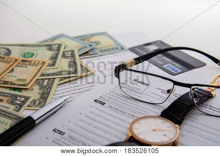 Concept the tax form W-8BEN and over things on the table