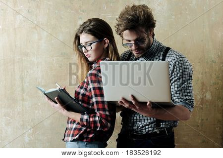 Pretty girl or beautiful woman with notebook and handsome man with laptop computer in checkered shirts on beige background. Young nerd couple of students in geek glasses. Education and technology