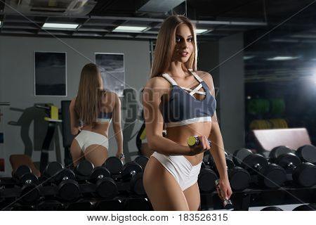 Slim sexy fitness trainer dressed in top and shirts posing with a dumbell in gym