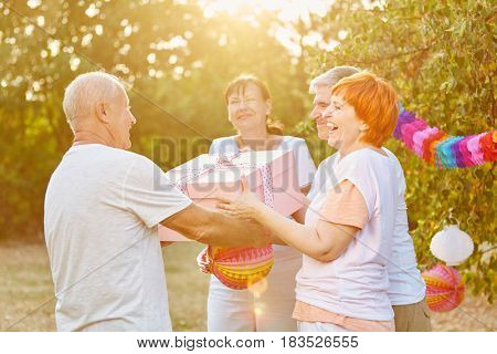 Seniors at a birthday party congratulate their friend with a gift