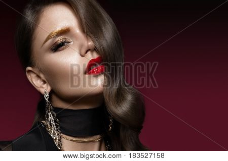 Beautiful girl with red lips and golden eyebrows, curls in Hollywood style. Beauty face. Photo taken in the studio.