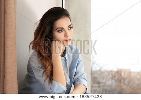 Beautiful young woman sitting on window sill at home