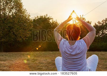 Senior woman making a yoga exercise in the nature in summer