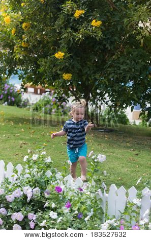 Cute Baby Boy Walking Barefoot On Green Grass In Park