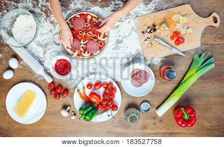 Top View Of Child Making Pizza With Pizza Ingredients, Tomatoes, Salami And Mushrooms On Wooden Tabl