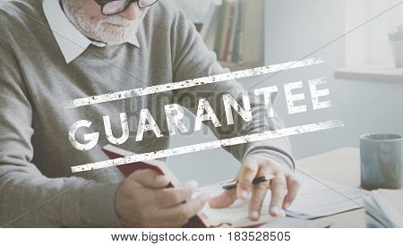 Senior man working on the table with guarantee word