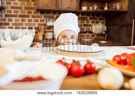 Little Girl Making Pizza Dough With Pizza Ingredients In Kitchen