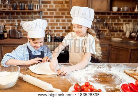 Little Children Making Pizza Dough With Pizza Ingredients On Foreground