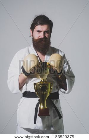 Bearded Smiling Karate Man In Kimono, Boxing Gloves, Champion Cup