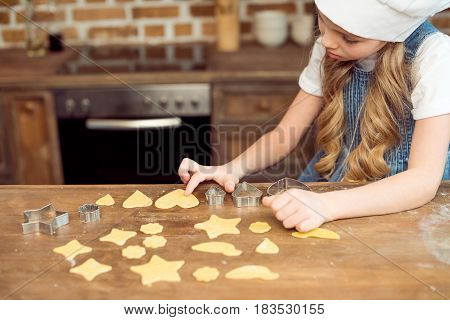 Side View Of Little Girl In Chef Hat Making Shaped Cookies In Kitchen