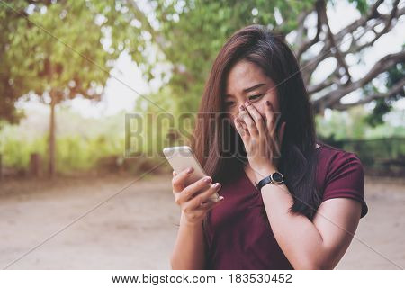 A beautiful asian woman looking at smart phone with feeling sad and cry in outdoor and green nature background