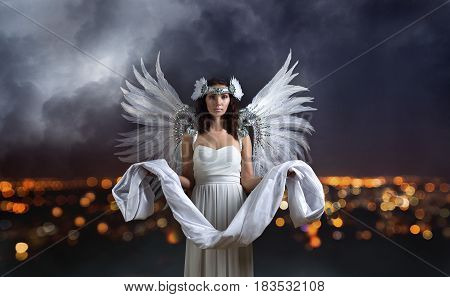 Young beautiful woman in white dress with angel wings and shroud in hands. Beautiful Professional Make-up perfect headdress with natural feathers and rhinestones. Night city and cloudy sky . poster