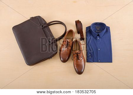 Mans shoes and shirt ,belt, bag on wood background