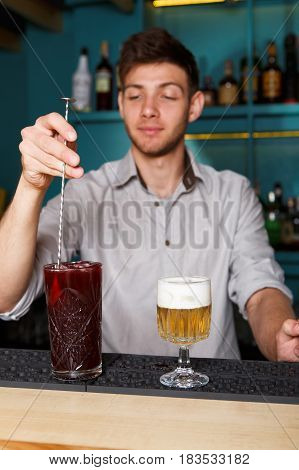Barman in bar interior stir ice in red berry alcohol cocktail. Professional bartender at work in night club. Service industry occupation. Vertical image