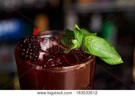 Closeup of healthy sweet berry non-alcoholic party cocktail at restaurant background. Refreshing drink with ice, blackberries and mint dusted with sugar