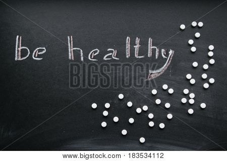 Chalk inscription be healthy and scattered tablets on a slate background