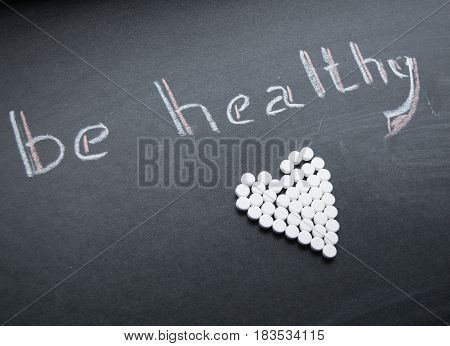 The chalk inscription be healthy and the heart of the tablets on the slate background