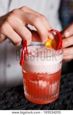 Barman's special - frothy exotic spicy alcohol cocktail with chili peppers and orange in restaurant at bar background. Glass on bar table, original and creative refreshing drink.