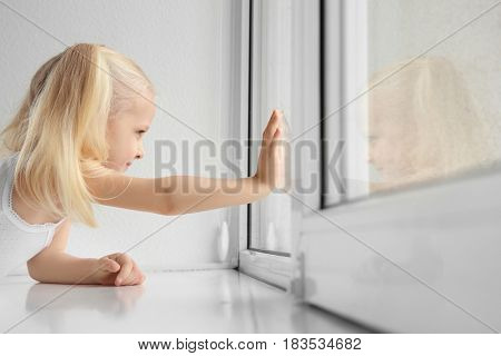 Cute little girl playing on windowsill