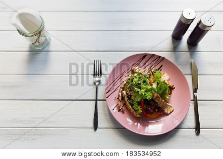 Restaurant food on white wood, top view with copy space. Turkey salad with orange, vegetables and lettuce on blue plate. Appetizing dish served with sauce, dinner meal.