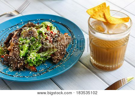 Restaurant food closeup on white wood. Beautifully decorated warm beef salad with sesame, vegetables and lettuce on blue plate. Appetizing meat dish served with beer and chips
