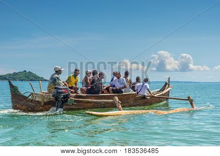 Ambatozavavy Nosy Be Madagascar - December 19 2015: Tourists with a guide crossing the inlets by outrigger canoe near the Ambatozavavy village in Nosy Be island Madagascar Africa.