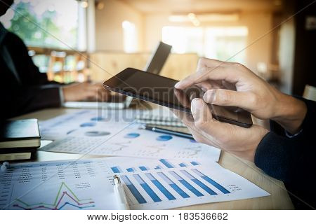 Team job succes. Closeup photo young hands business managers holding tablet working with new startup project in office.Analyze document plan Contemporary notebook on wood table.