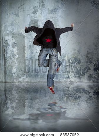 Levitation. Young man break dancing on wall background