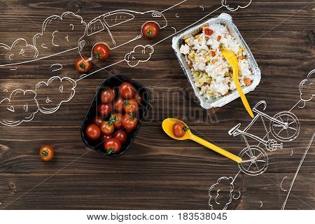 Brighten your life. Top view of cherry tomatoes lying on the table near cooked rice and plastic spoons