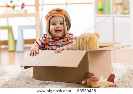 Happy pilot aviator baby boy with teddy bear toy plays in cardboard box