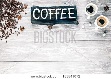Background of light textured wooden boards with coffee beans, white cups of black coffee and spices. Wood signboard with text 'Coffee'