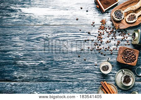 Background of black textured wooden boards with coffee beans, ground coffee and spices. Top view. Copy space