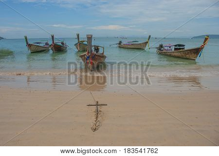 Traditional long tail boat on Railay Beach with blue sea and blue sky background, Krabi, Thailand.