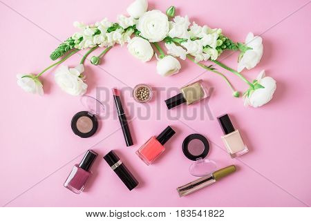 Feminine desk with woman cosmetics and white flowers on pink background. Flat lay, top view. Beauty background