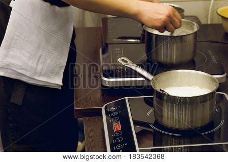Cook's hands preparing food on two electric plates