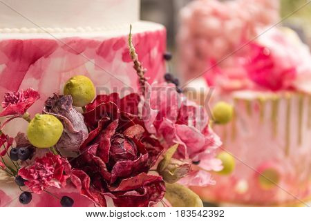 Decorative flowers from pastry mastic on cake, blurred background for copy space