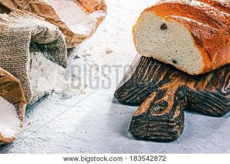 Homemade wheat bread on rustic wooden board next to packs of flour and sugar on the concrete background. Close up