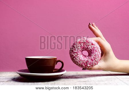 Hand Holding colorful donut with sprinkles on a wooden table and pink background. Cup of coffee. Two types of donuts. Cake and sweet. Food detail. Close up. Pastel color