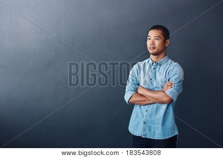 Casually dressed young Asian designer standing confidently with his arms crossed against a gray wall in an office
