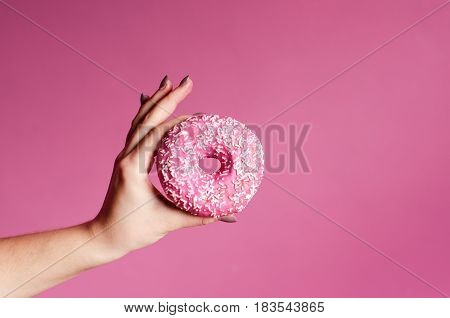 Hand Holding colorful donut with sprinkles on a wooden table and pink background. Two types of donuts. Cake and sweet. Food detail. Close up. Pastel color