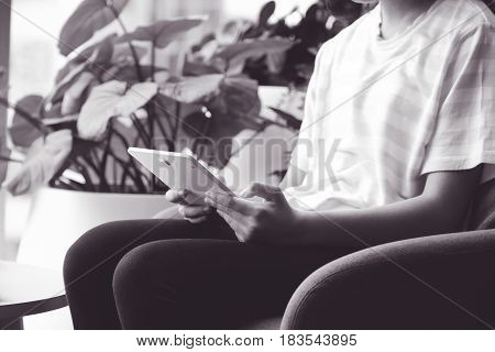 Woman using tablet while sitting on sofa in casual lifestyle black and white tone woman on phone concept