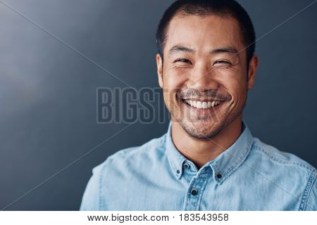 Portrait of a casually dressed confident young Asian designer smiling while standing against a gray wall in an office
