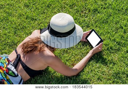 Woman in swimwear lying on grass and reading ereader