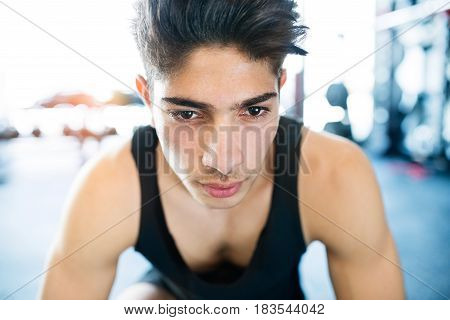 Young fit hispanic man in black sleeveless shirt in modern crossfit gym resting