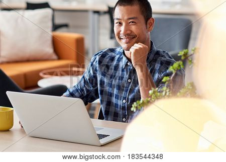 Close up portrait of a young Asian designer smiling confidently while sitting alone at a desk in a modern office working on a laptop