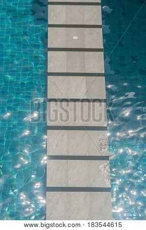 Concrete walkway across swimming pool with blue green water background.