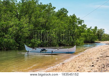 Ambatozavavy Nosy Be Madagascar - December 19 2015: Traditional wood pirogue with outrigger on the shore of the fishing village on the Nosy Be island Madagascar.